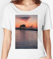 Stilt house in silhouette over the sea Women's Relaxed Fit T-Shirt