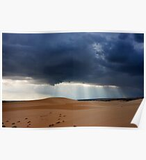 Storm clouds with piercing sunrays covering desert landscape. Poster
