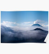 Volcanoes between white clouds of mist under a blue sky. Poster