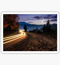 countryside road with car lights at night Sticker