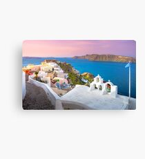 Oia town on Santorini island, Greece. Traditional and famous houses and churches with blue domes over the Caldera, Aegean sea Canvas Print