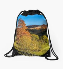 red tree  behind the fence on hillside Drawstring Bag