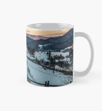fence on snowy mountain slope near the forest in winter Mug