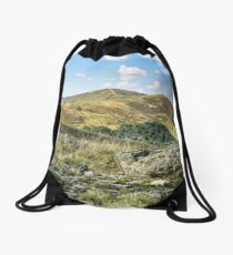 mountain landscape with stones in the grass on hillside and blue sky Drawstring Bag