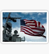 USS Cowpens flies a large American flag during a live fire weapons shoot. Sticker