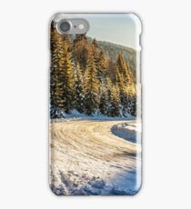 snowy road through spruce forest in mountains iPhone Case/Skin