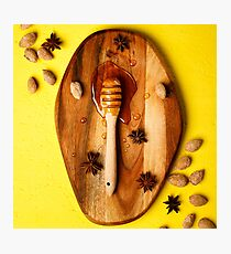 Honey dipper with nuts and spices on yellow background Photographic Print