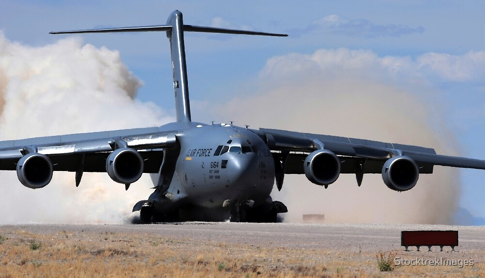 A C-17 Globemaster lands on the runway. by StocktrekImages
