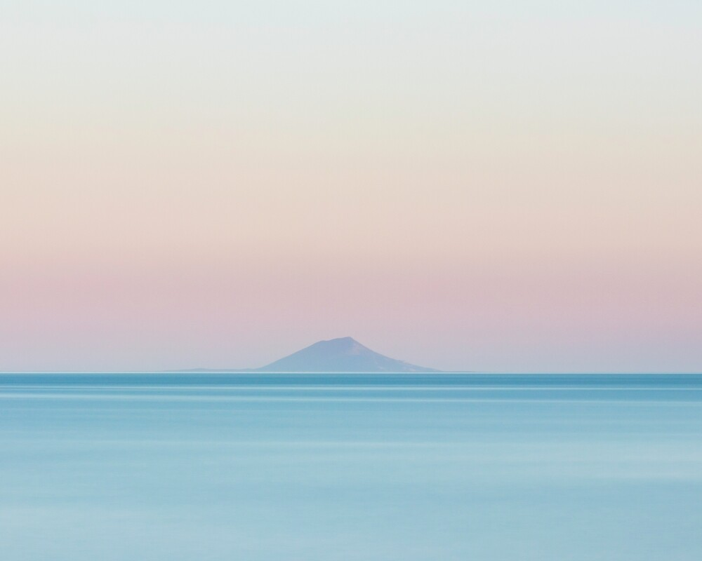 Island silhouette on horizon at sunset by Patrik Lovrin