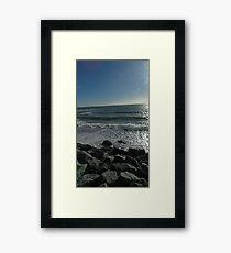 Waves crashing against the rocks Framed Print