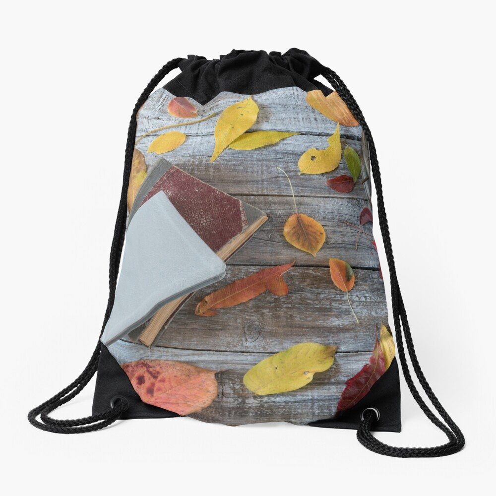 Vntage books and clock on wooden table. Autumn composition. Drawstring Bag