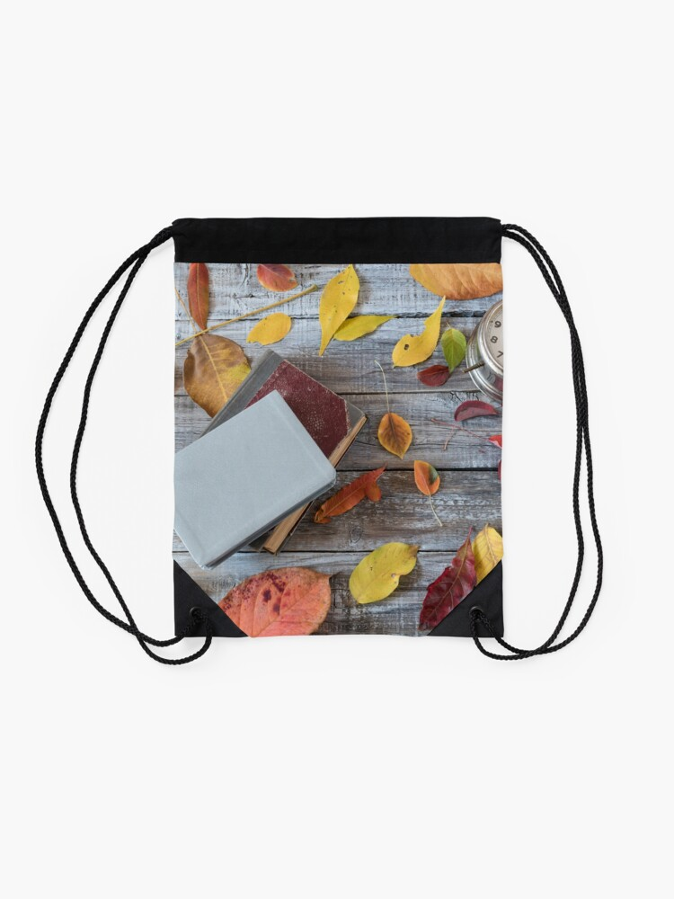 Alternate view of Vntage books and clock on wooden table. Autumn composition. Drawstring Bag