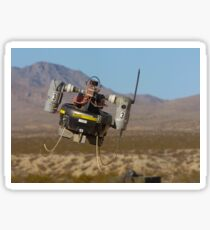 A Micro Air Vehicle flies over a simulated combat area. Sticker