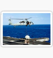An MH-60R Seahawk helicopter places cargo onto the flight deck of USS Nimitz. Sticker