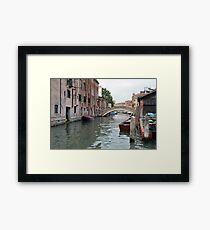 Canal in Venice, Italy, with boats and typical architecture  Framed Print