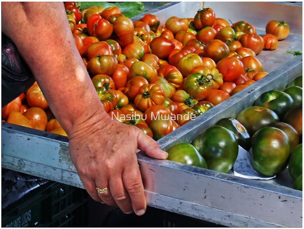 Tomatoes and Hand by Nasibu Mwande