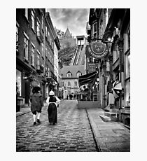 Two persons dressed in medieval costumes walking up the Rue Sous Le Fort street in old Quebec City Black and white art print Photographic Print