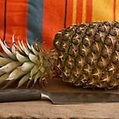 Ripe pineapple and a large knife on the table by mrivserg