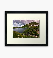 lake in mountains with snow on hillside Framed Print