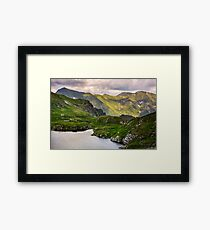 lake in mountains with grass on hillside Framed Print