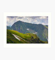 rocky edge on grassy hillside with snow  Art Print
