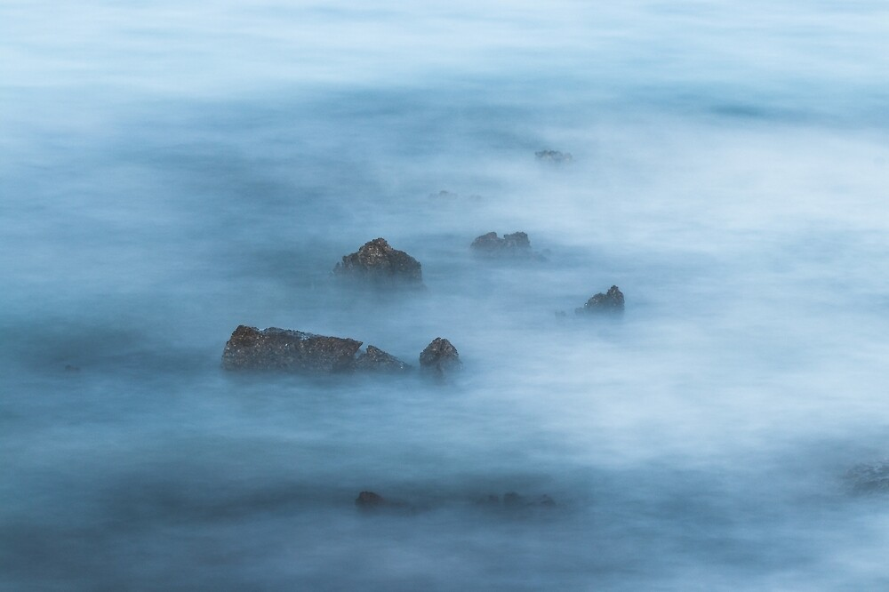 Misty blue long exposure of rocks in sea by Patrik Lovrin