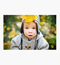 Close up of cute curious little boy with yellow leaf in a cap Photographic Print
