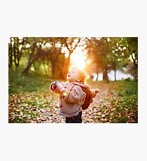 Happy kid boy in autumn park walking outdoors Photographic Print