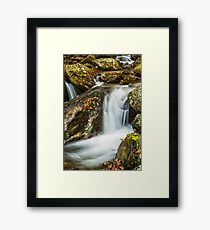 Small waterfall flowing over rocks in Autumn Framed Print
