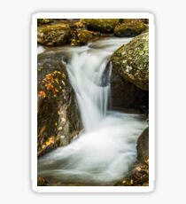 Small waterfall flowing over rocks in Autumn Sticker