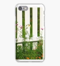 White fence on green grass with flowers. iPhone Case/Skin