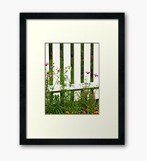 White fence on green grass with flowers. Framed Print
