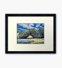 Old moss stones against blue sky. Framed Print