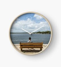 Teenage boy sitting on a wood bench looking out the water Clock