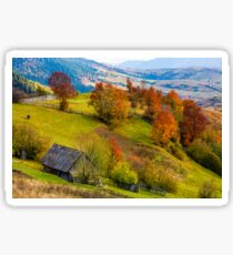 woodshed on grassy hillside with reddish trees Sticker