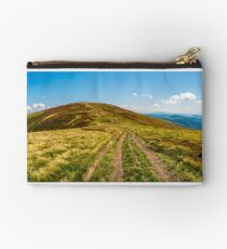 panorama with dirt road through mountain ridge Studio Pouch