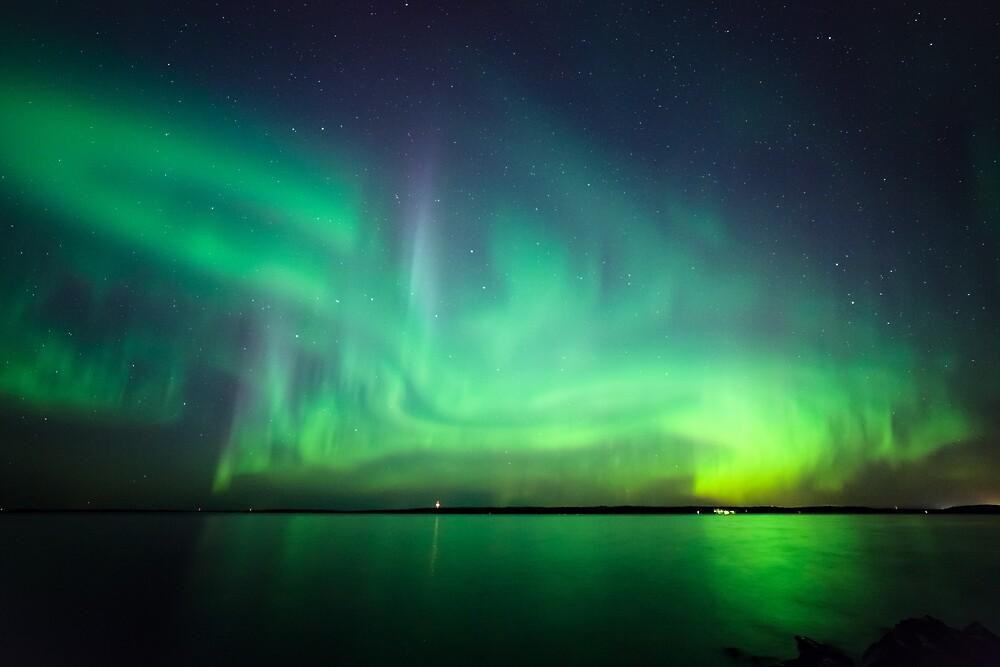 Northern lights over lake by Juhani Viitanen