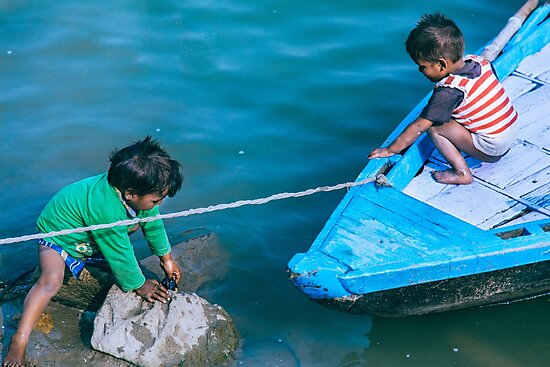 Two kids playing in the river by soytribu