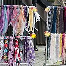 Selling scarves on a windy day. by Gabriele Maurus