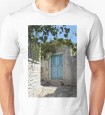 Old Greek village with white stone walls and blue door  T-Shirt