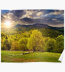 fence on hillside meadow in mountain at sunset Poster