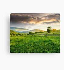 fence on hillside meadow in mountain at sunrise Canvas Print