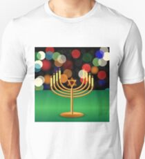Metal Menorah with Burning Candles is on Green Table. T-Shirt