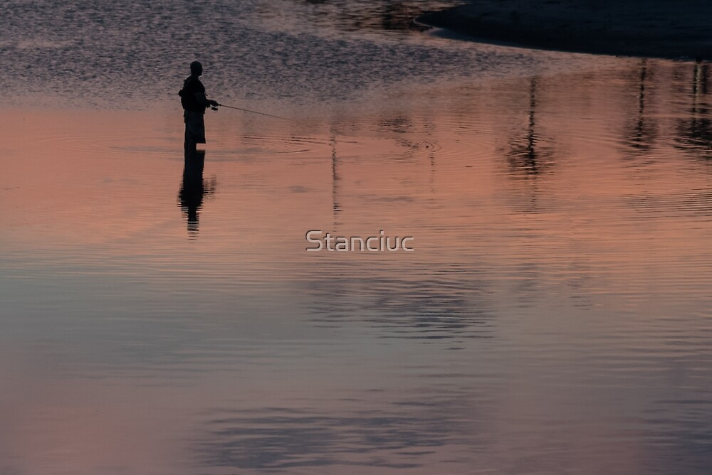 Silhouette of unrecognisable fisherman in the lake on sunset by Stanciuc
