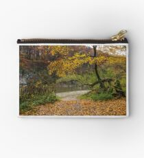 yellow trees on rocky shore of the river Studio Pouch