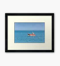 Bright blue sea and a fisherman boat Framed Print