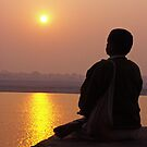 Man in meditation in front of sun - India by Christophe Dur