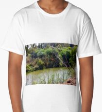 The dry tree bent towards the river, which flows among the green plants landscape Long T-Shirt