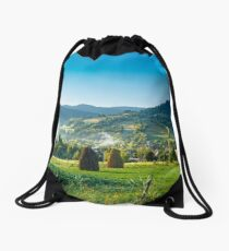 field with haystack on hillside in mountains Drawstring Bag
