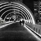 People walking on bridge at night by Ewan Arnolda